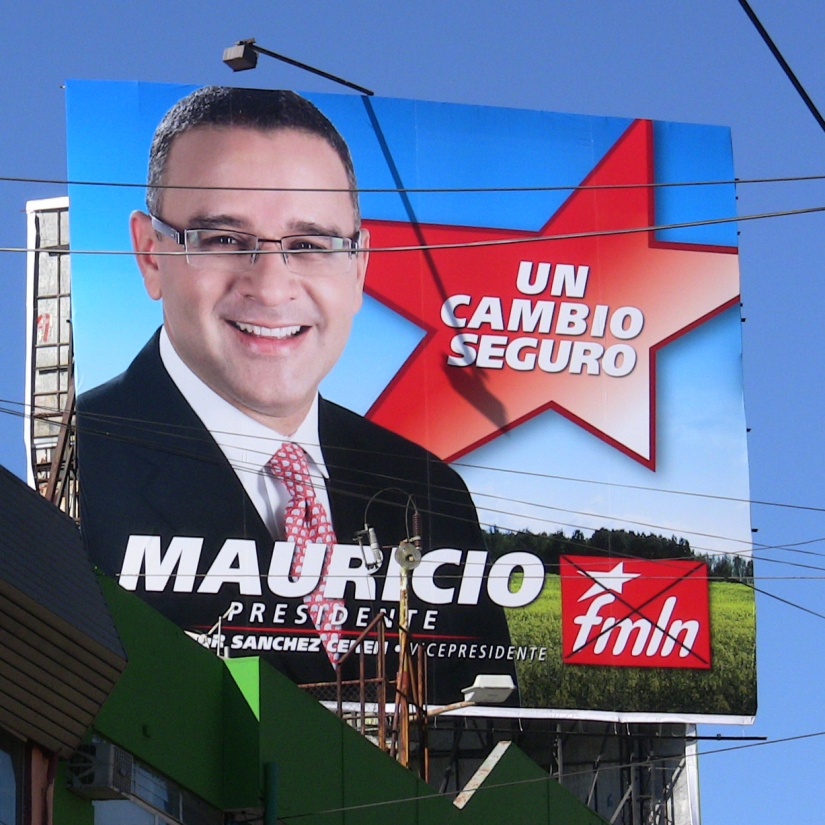 The billboard shows Funes and the FMLN flag.